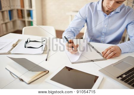 Young employee reading papers at workplace