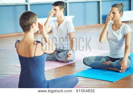 Girl and guy repeating yoga exercise after their teacher in gym