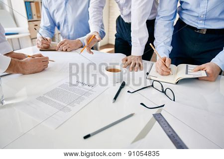 Group of architects discussing documents, ideas and making notes