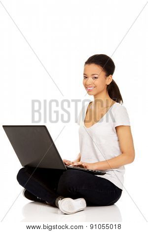 African teen sitting cross legged with laptop.