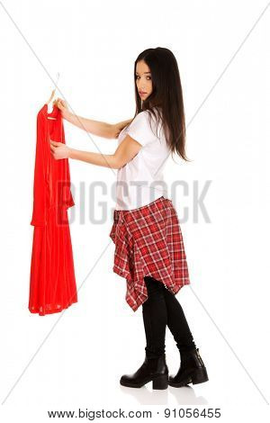 Beautiful teen woman buying red dress.