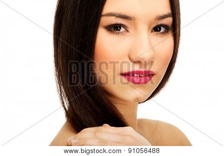 Beautiful woman with full make up touching shoulder.