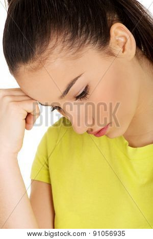 Casual depressed teen woman touching head.