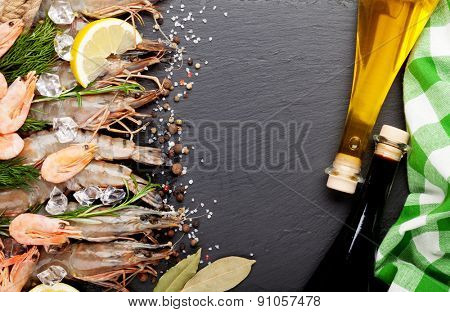 Fresh prawns with spices and condiments on black stone background. Top view with copy space
