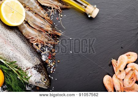 Fresh raw sea food with spices on black stone background. Top view with copy space