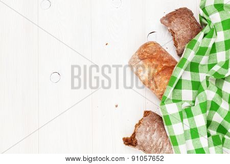 White and brown ciabatta on wooden table. Top view with copy space