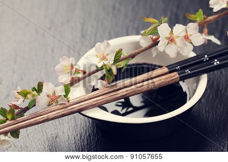 Japanese sushi chopsticks, soy sauce bowl and sakura blossom on black stone background