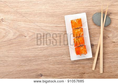 Sushi maki with tobiko on bamboo table with copy space
