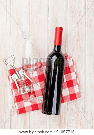 Red wine bottle, glass and corkscrew on white wooden table background. Top view with copy space