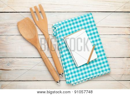Kitchen utensil and notepad over white wooden table background. View from above with copy space