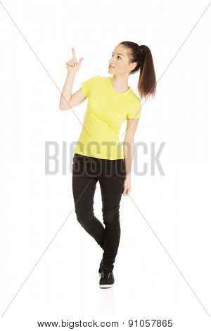 Young student woman pointing up.