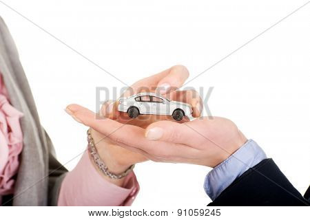 Caucasian businesswoman giving small car to her partner.