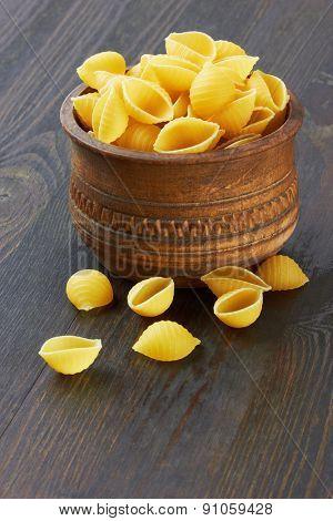 Conchiglioni italian pasta in wood bowl, on wood background
