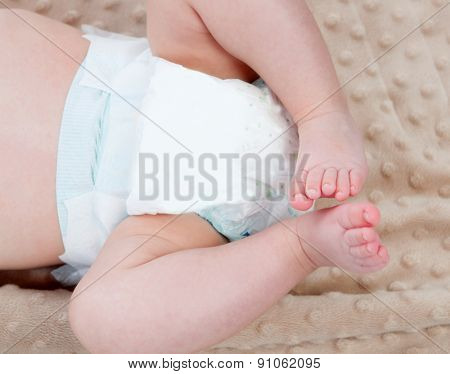 Legs of a baby with diaper on a blanket