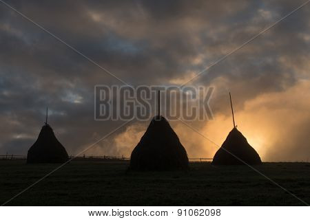 three haystack in foggy field