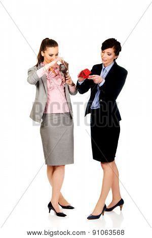 Unhappy two businesswomen with empty wallets.