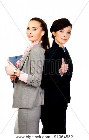Happy smiling two businesswomen with thumbs up gesture.