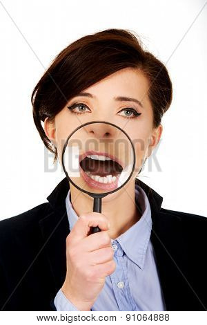Funny businesswoman with magnyfing glass on teeth.