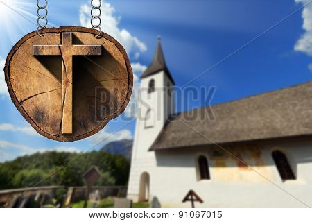 Wooden Cross On Tree Trunk With Small Church