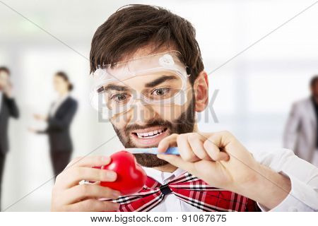 Determined man wearing suspenders cutting heart model with scalpel.