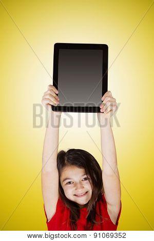 Happy smiling little girl holding tablet