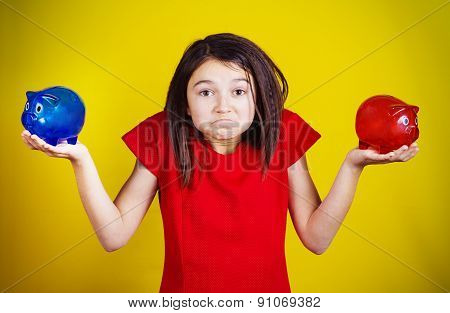 Confused little girl holding two piggy banks one red another blue wondering what to do.