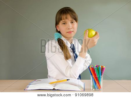 The schoolgirl sitting at a desk in the classroom, dreaming,