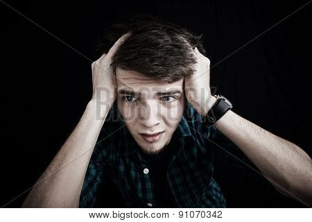 Stressed young student,men portrait, sad, bothered, holding hands on his head.