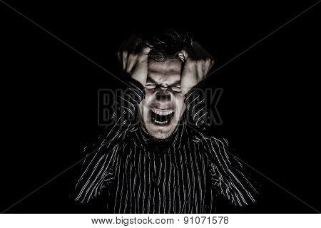 Stressed, aggressive, frustrated portrait of a young student, man,screaming holding his fists