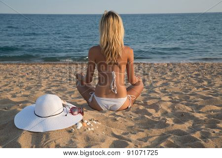 Young Woman Meditating On The Beach With Sea In Background.