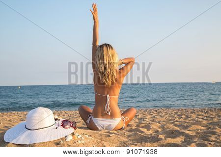 Young Woman Sitting On The Beach In Bikini And Relaxing.