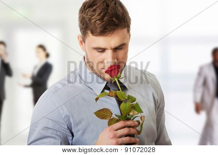 Young handsome man holding red rose.