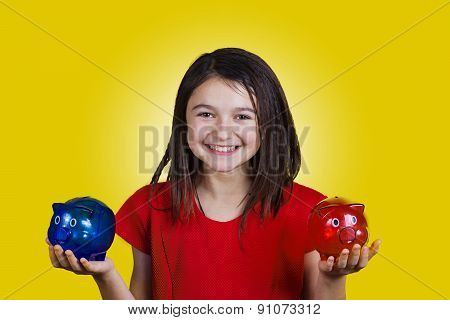 Smiling little girl holding two piggy banks one red another blue.Economy,Business
