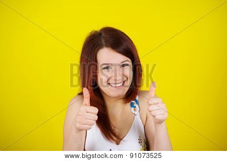 Happy surprised  young  woman very excited holding thumbs up isolated on yellow background.