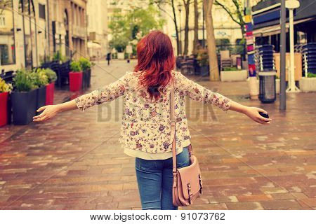 Freedom-Young woman with raised hands in a city.Young woman walking with raised hands feeling free
