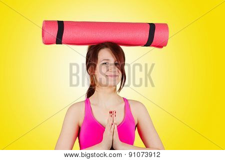 Sporty fit healthy smiling beautiful woman, red head girl holding  an yoga mat on head.Exercise, fit