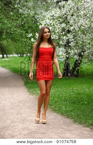 Beautiful young woman in red dress against the background spring flowers trees