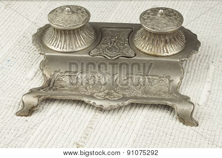 old Art Nouveau inkwell on desk, metal alloy