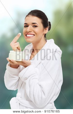 Woman in bathrobe applying face cream.