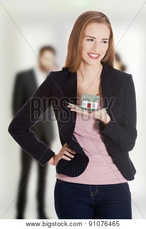Smiling businesswoman holding a house.
