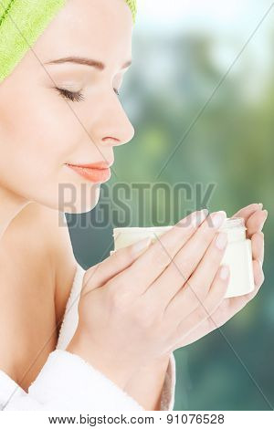 Woman in bathrobe with body lotion.