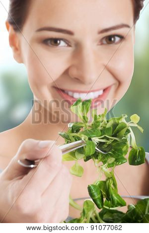 Healthy young woman eating lettuce.