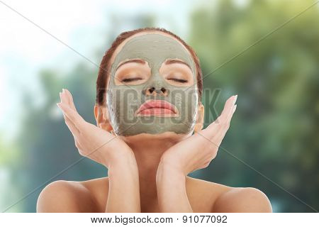 Beautiful spa woman with clay facial mask.
