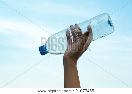 Woman hand hold a bottle of water in to sky