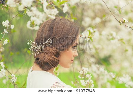 Beautiful Girl in spring garden. Girl with white flowers, spring time.