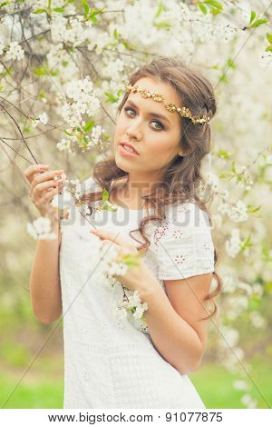 Beautiful Girl in white dress walking in spring garden. Girl with flowers, spring time.