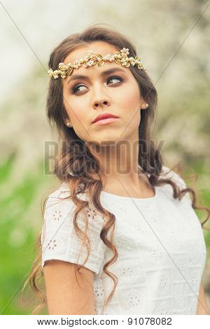Beautiful Girl with golden tiara on her head in spring garden, spring time.