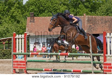 Closeup Of Young Horsewoman Jumping. Horizontally.