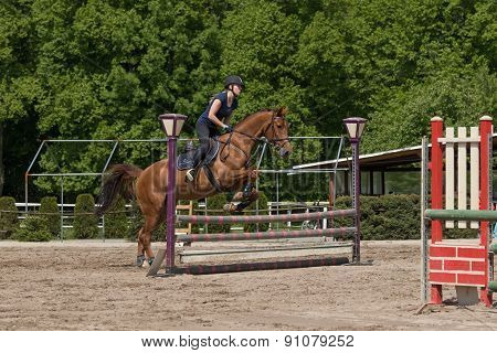 Young Horsewoman Is Jumping At Equestrian Race