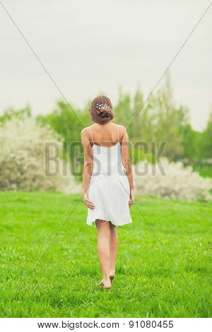 Beautiful Girl in white short dress walking in spring garden, rear view